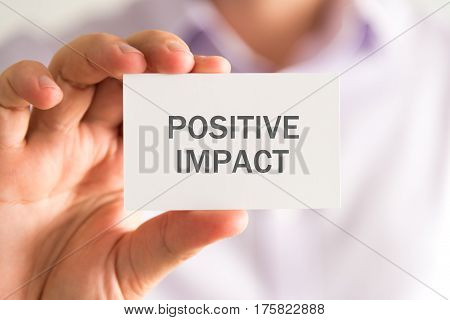 Businessman Holding A Card With Positive Impact Message