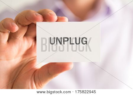 Businessman Holding A Card With Unplug Message