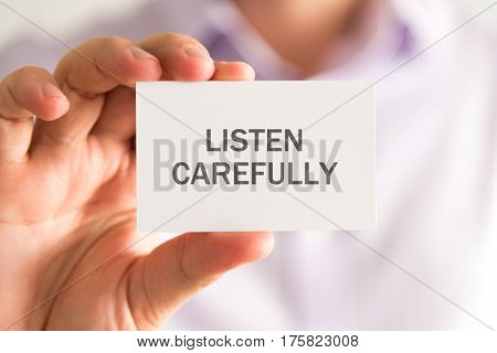 Businessman Holding A Card With Listen Carefully Message