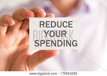 Businessman Holding A Card With Reduce Your Spending Message