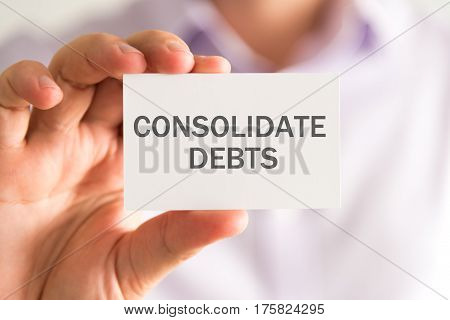 Businessman Holding A Card With Consolidate Debts Message