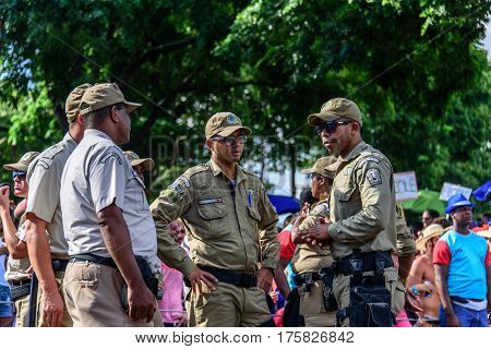 RIO DE JANEIRO, BRAZIL - FEBRUARY 28, 2017: Group of talking policemen during Bloco Orquestra Voadora on the background of crowd of people, Carnaval 2017