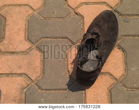 black old and wornout shoe on brick floor