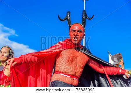 RIO DE JANEIRO, BRAZIL - FEBRUARY 28, 2017: Young man in a costume of devil with red face, big black horns and black and red cloak walking on stilts during Bloco Orquestra Voadora at Carnaval 2017
