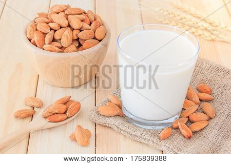 Almond milk in glass with almonds on wooden table Close up