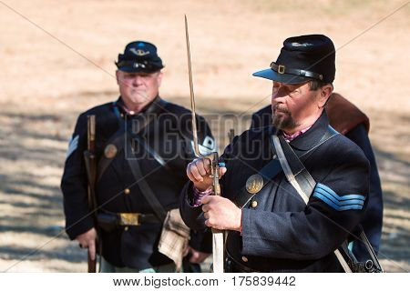 KENNESAW, GA - NOVEMBER 2016:  A Civil War reenactor wearing a union uniform demonstrates how to attach a bayonet to a musket at a firing demonstration put on at Kennesaw Mountain National Battlefield Park in Kennesaw GA on November 20 2016.