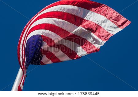 An American flag curls in interesting pattern as wind blows it on flag pole.