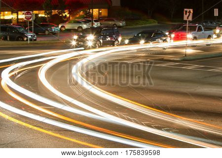 Motion blur of car headlights streaking as vehicle turns at busy intersection.