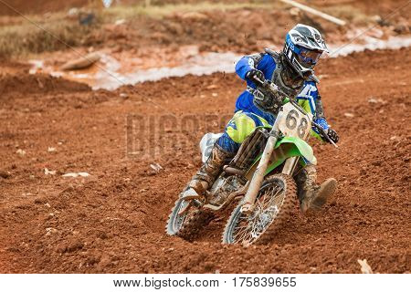 MONROE, GA - DECEMBER 2016:  A rider negotiates a turn on a muddy track at a motocross race at the Scrubndirt Track in Monroe GA on December 3 2016.