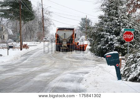 snowplow truck removing snow on residential street