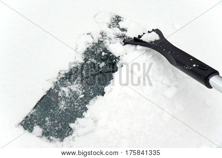 ice scraper removing ice on windshield of car