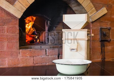 Small wooden windmill stands on the table next to the Russian stove.