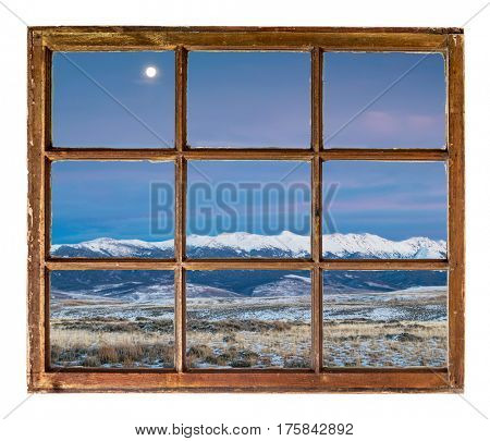 full moon over snowy Medicine Bow Mountains, North Park near Walden, Colorado as seen through vintage sash window
