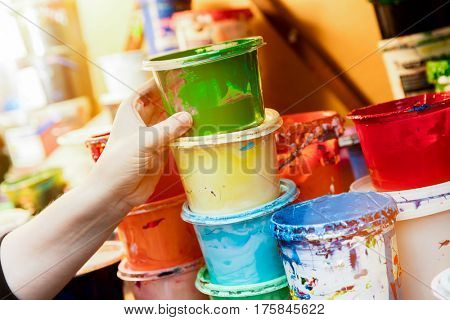 Artist reaching for a liquid paint container. Working in a workshop