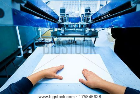 Worker preparing print screening metal machine. Industrial printer. Manufacture work. First person perspective.