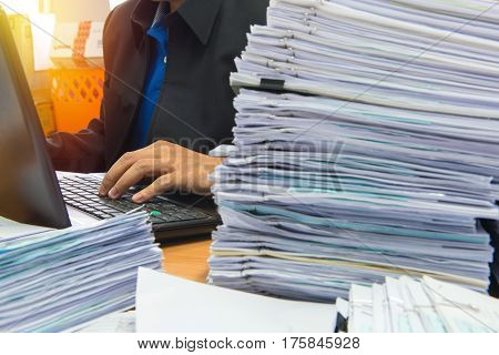 Documents On Desk Stack Up High Waiting To Be Managed