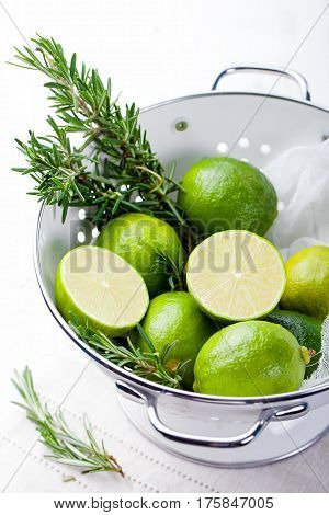 Fresh Limes And Rosemary In White Enamel Colander.