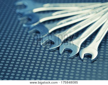 Chrome wrench assortment on a modern dark background with space for text selective focus