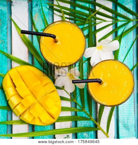Mango smoothie juice and fresh mango on a outdoor tropical background. Copy space. Top view.