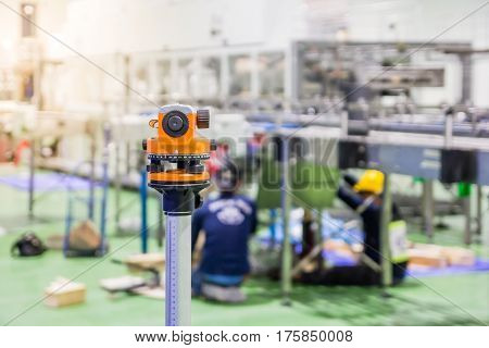 Construction surveyor equipment theodolite level tool during workers installing machine at background