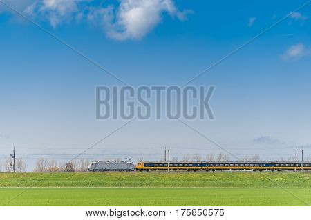 Passenger Train Moving Along Green Field