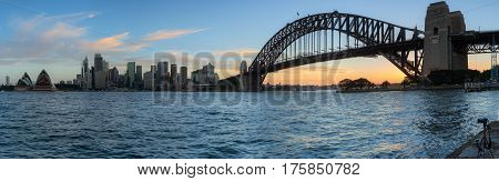 SYDNEY AUSTRALIA - March 12 2017: Panorama of Sunset at Sydney Harbour Bridge and Opera House illuminated with colourful light Over 10 millions tourists visit Sydney every year