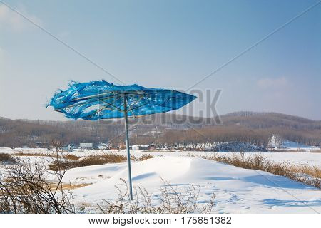 Abandoned Makeshift Sun Umbrella. Winter Snowy Landscape.