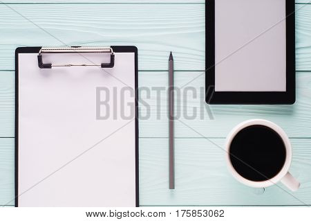 Folder clipboard with white blank paper sheet pencil cup of coffee and tablet with copy space top view. Business concept. Blank clipboard on wooden background flat lay.