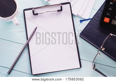 Business objects (black clipboard with blank sheet of paper pencil glasses envelopes and calculator) top view. Space for text. Workplace with office supplies and cup of coffee flat lay. Copy space.