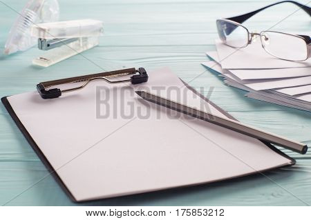 Business objects (black clipboard with blank sheet of paper pencil glasses envelopes). Space for text. Workplace with office supplies. Copy space.