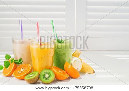 Freshly blended fruit smoothies in glasses on a white wooden background. Fresh fruit cocktails of various colors and tastes kiwi banana orange. Assorted fruit shakes. Diet concept.