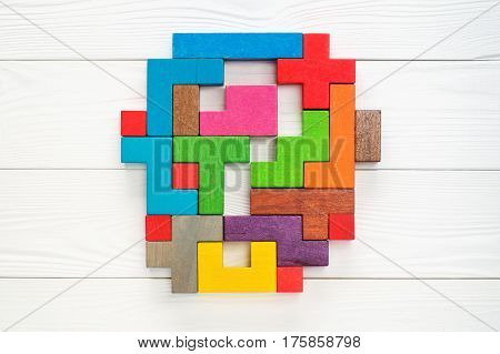 Concept of creative logical thinking. Different colorful shapes wooden blocks on white wooden background flat lay copy space. Abstract question mark made of wooden blocks top view. The hidden question.