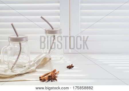 Two empty vintage glass with drinking straw against vintage white wooden shutters background. Vintage mason jars with cinnamon and star anise on white window sill.