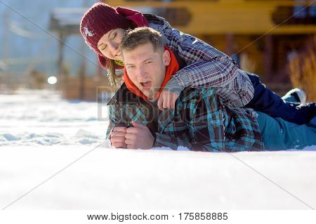 Young couple lies on snow. Girl has got on guy's back. Serene winter day. Young people with pleasure flounder in snow.