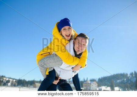 Young man holding his girlfriend on his shoulders. Girl embraces guy for neck. Young people look in the camera and cheerfully smile. Against the background of the blue sky.