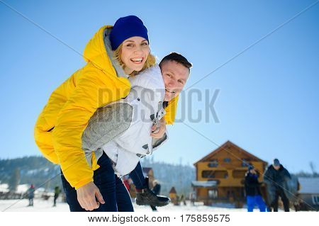 Young man holding his girlfriend on his shoulders. Girl embraces guy for neck. Young people look in the camera and cheerfully smile. Against the background of mountains and blue sky.