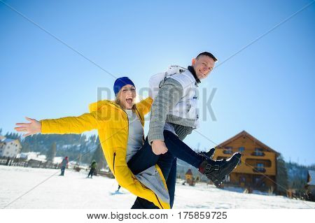Guy and a girl are having fun in the courtyard of a cottage in a ski resort. A young man carries a girl on her back. She is laughing. Good winter day. Sun sky mountains.