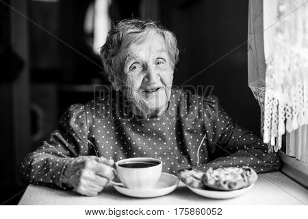 Grandma. Elderly woman drinking tea with pastries sitting at the table. Black-and-white photo.