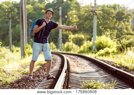 Young Man in Summer Travel Clothing hitch hiking Train on Railroad in wild Forest in rural Location with Sunlight Background