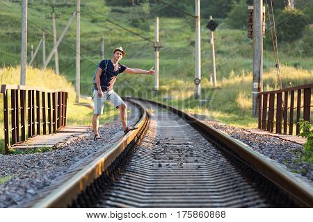 Young Person catching Train showing hitch-hiking Hand Sign on dirty Countryside Railroad Bridge with grassy Meadow on Background