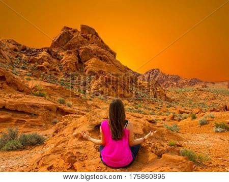 Young woman meditating outdoors in Valley of Fire State Park, Nevada, USA at sunset