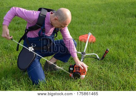 The man starts a weed trimmer on a lawn