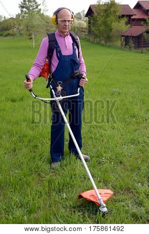 Man wearing ear protectors and glasses mowing grass with petrol weed trimmer