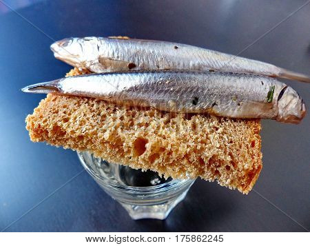 A bread, spicy salting anchovy  and a glass of vodka. Closeup. Gorgeous home appetizer under a glass of vodka. Natural food. Traditional Dishes of Russian Cuisine.