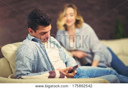 Jealous woman spying her husband mobile phone while he is reading a message