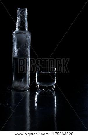 Bottle Frozen Vodka And Glass On Black Background