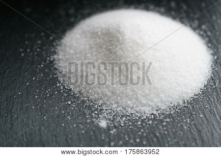 heap of extra small salt on black slate background, shallow focus