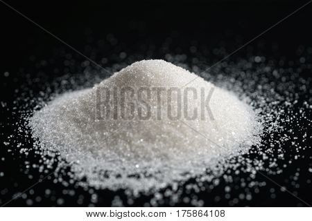 sugar pile on black background, closeup photo
