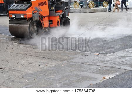 Road repair compactor lays asphalt. Roadworks on laying of a new of asphalt. Repair pavement and laying new asphalt patching method outdoors.