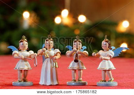 Four Christmas Angels Making Music in front of Bokeh Christmassy lights